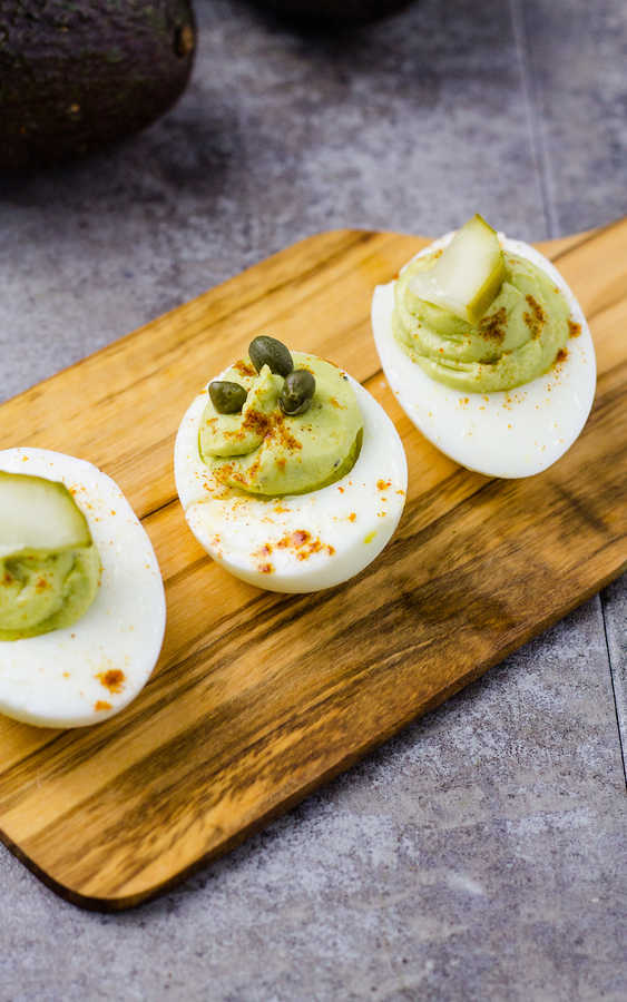 three hard boiled eggs with avocado on a wood plate