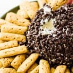 hand dipping graham cracker stick in to Cannoli Cheese Ball