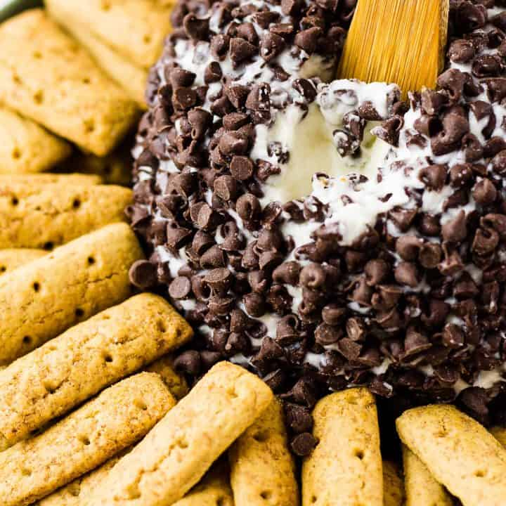 close up of Cannoli Cheese Ball with graham cracker cookie sticks on a plate