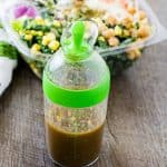 Roasted Ginger Vinaigrette Dressing and a salad on a wood surface