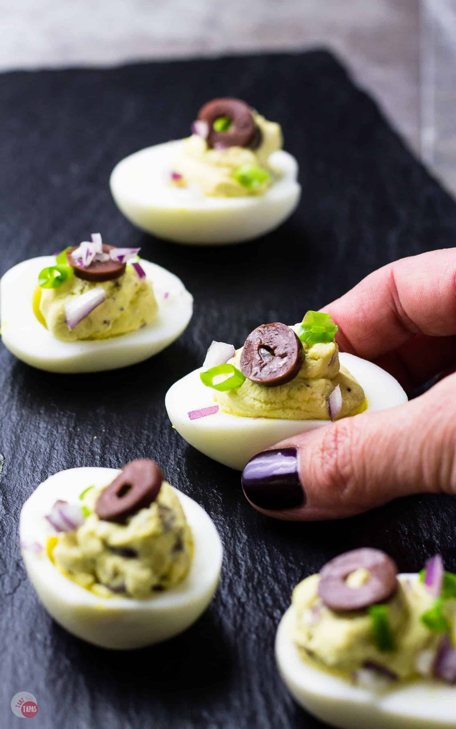 Mediterranean Deviled Eggs on a black platter