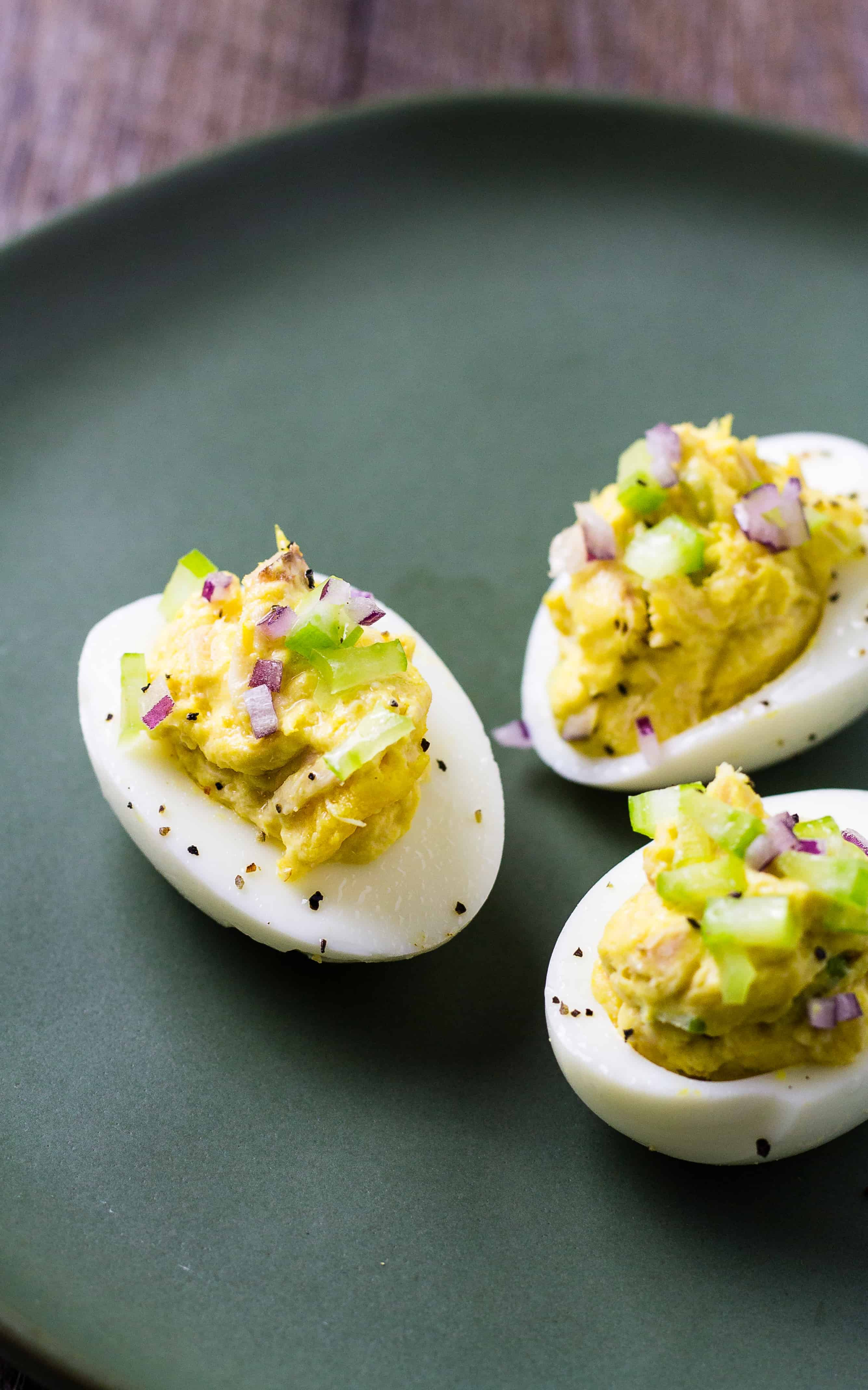 three deviled eggs with tuna salad on a plate