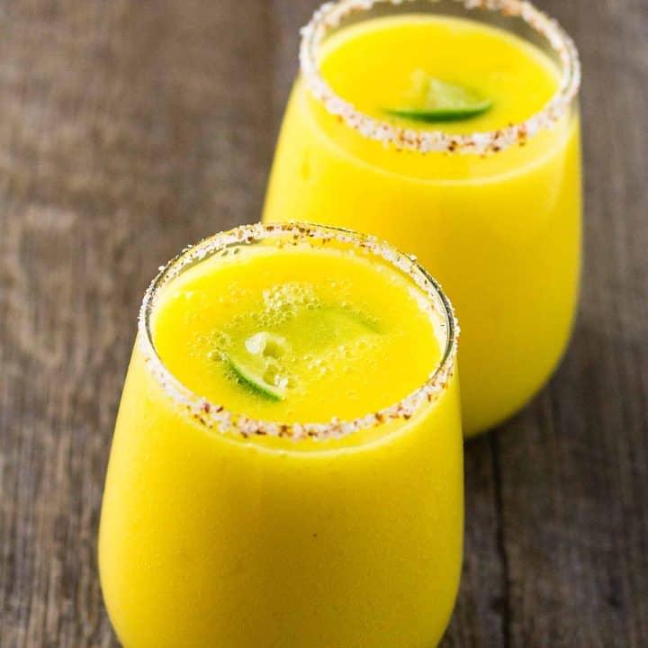 2 Spicy Mango Margarita with a Spicy Tajín Salt rim on a table