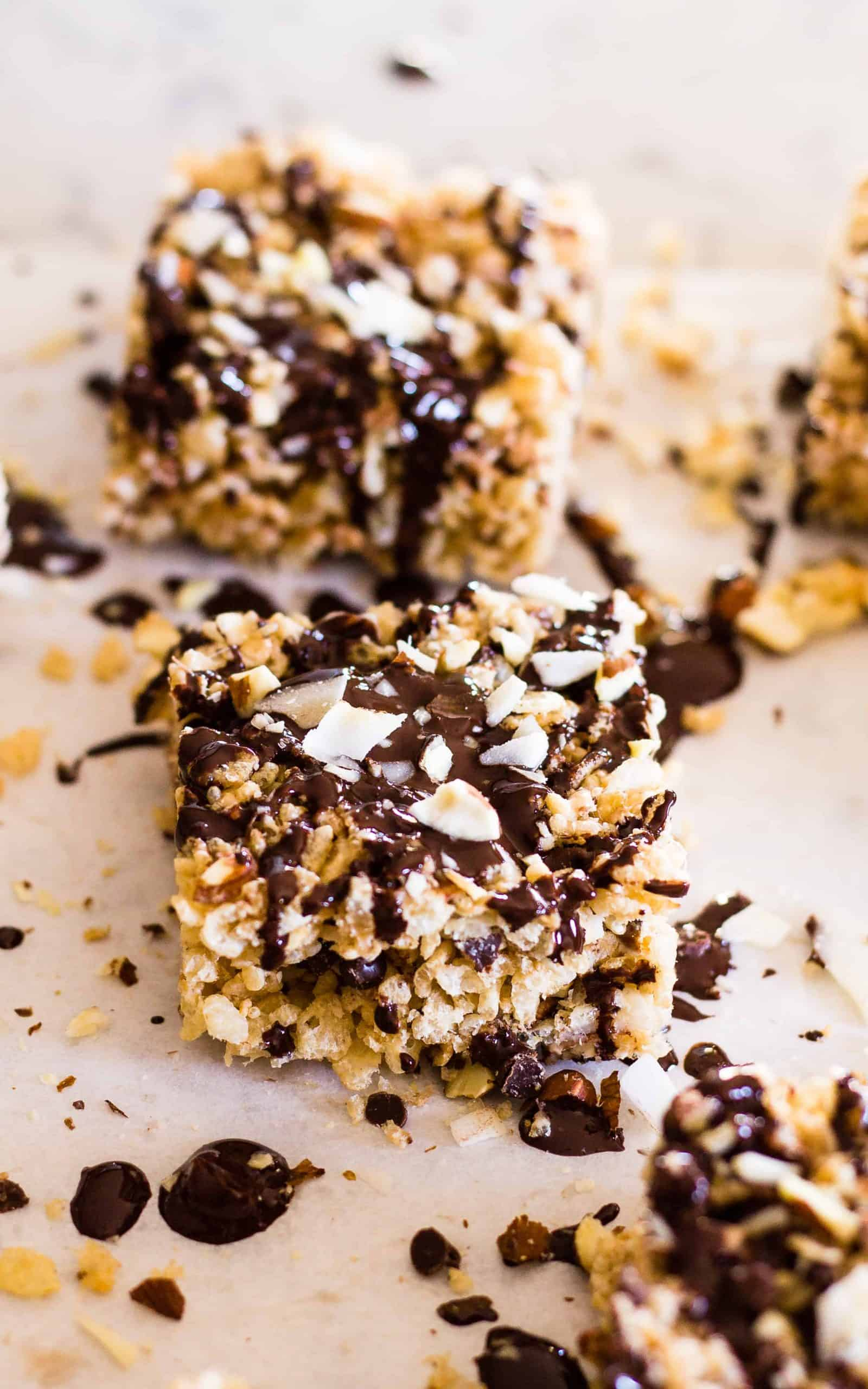 Recently drizzled Almond Joy Rice Krispie squares on parchment paper