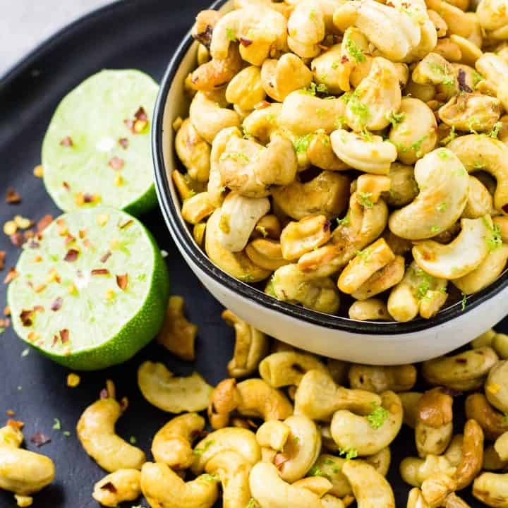 Zesty Chili Lime Cashews in a white bowl on a black plate with more cashews and a lime.
