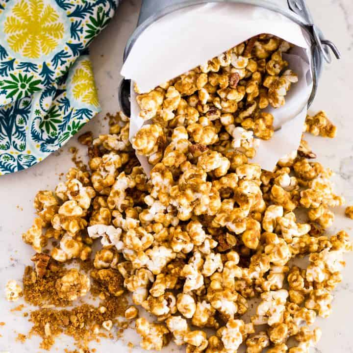 overhead of Grandma's Caramel Corn spilling out on to table from container