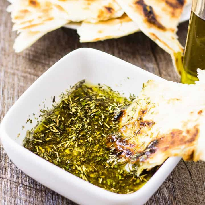 Greek Dipping Oil in a white bowl with Pita on a wood table