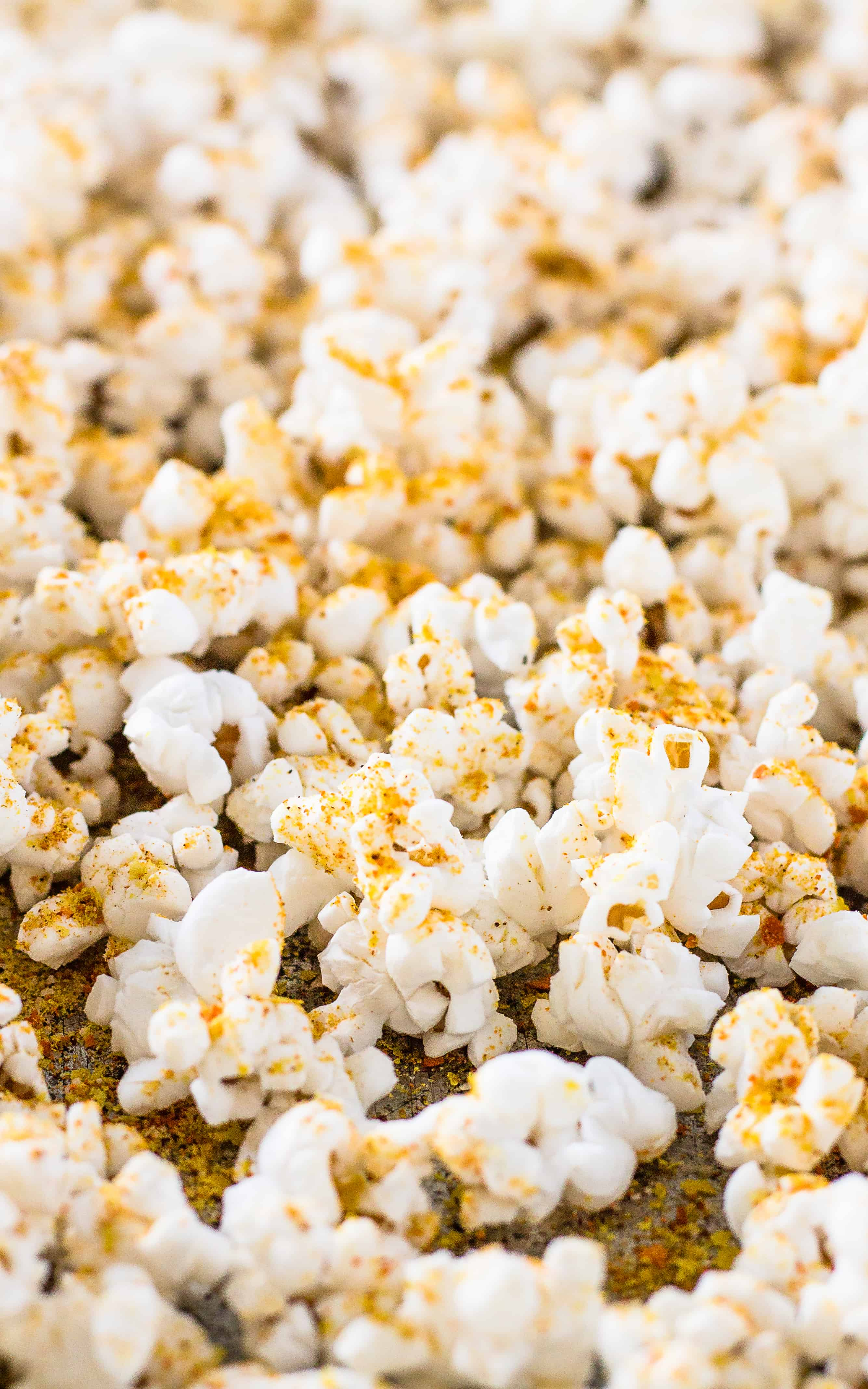 Spread the popcorn on the pan before sprinkling the Spicy Nacho Popcorn