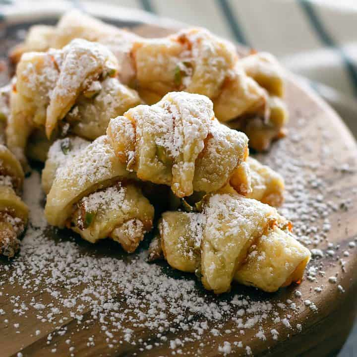 Rugelach on wooden platter covered in powdered sugar