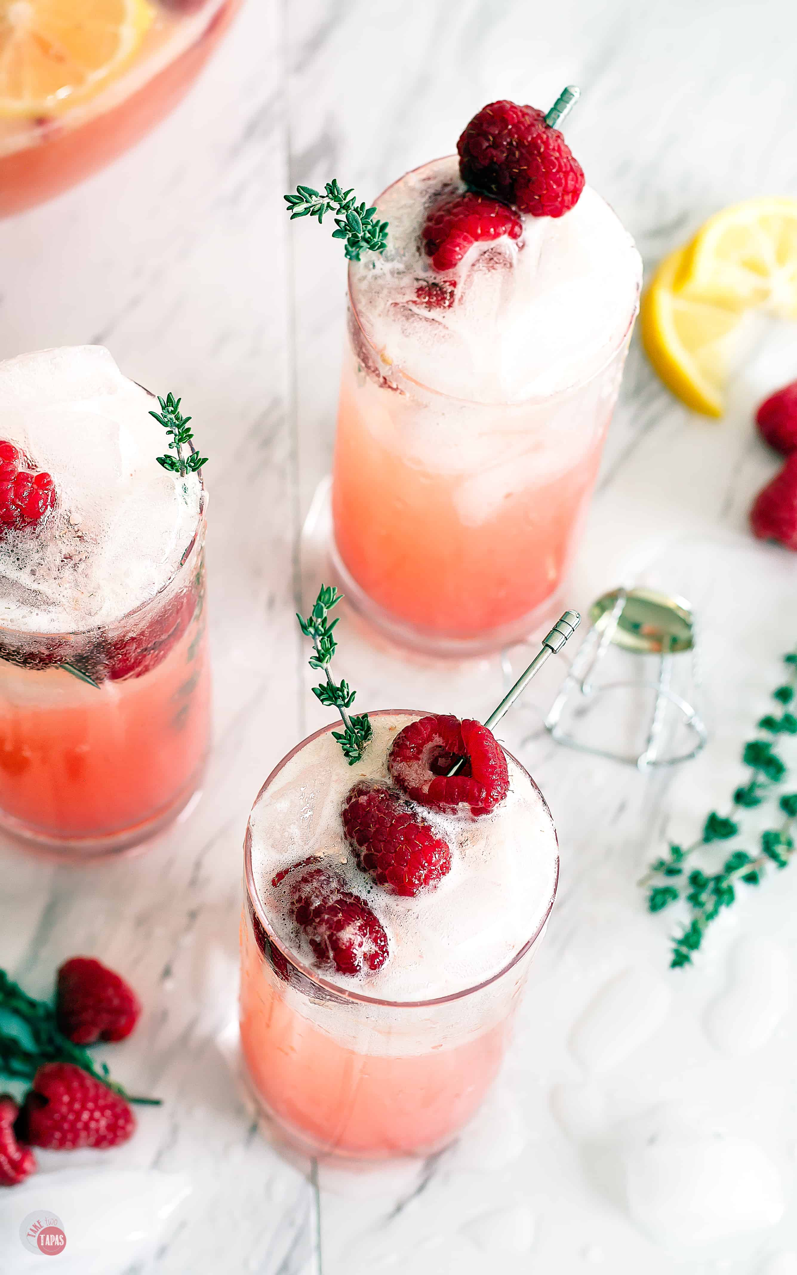 three glasses of the drink with raspberry garnish