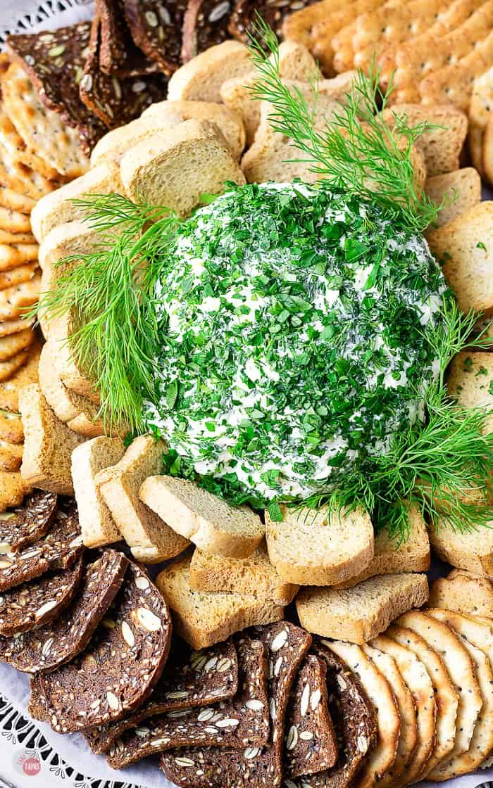 cheese ball covered with herbs surrounded with crackers