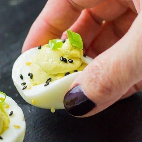 hand holding ginger wasabi deviled egg