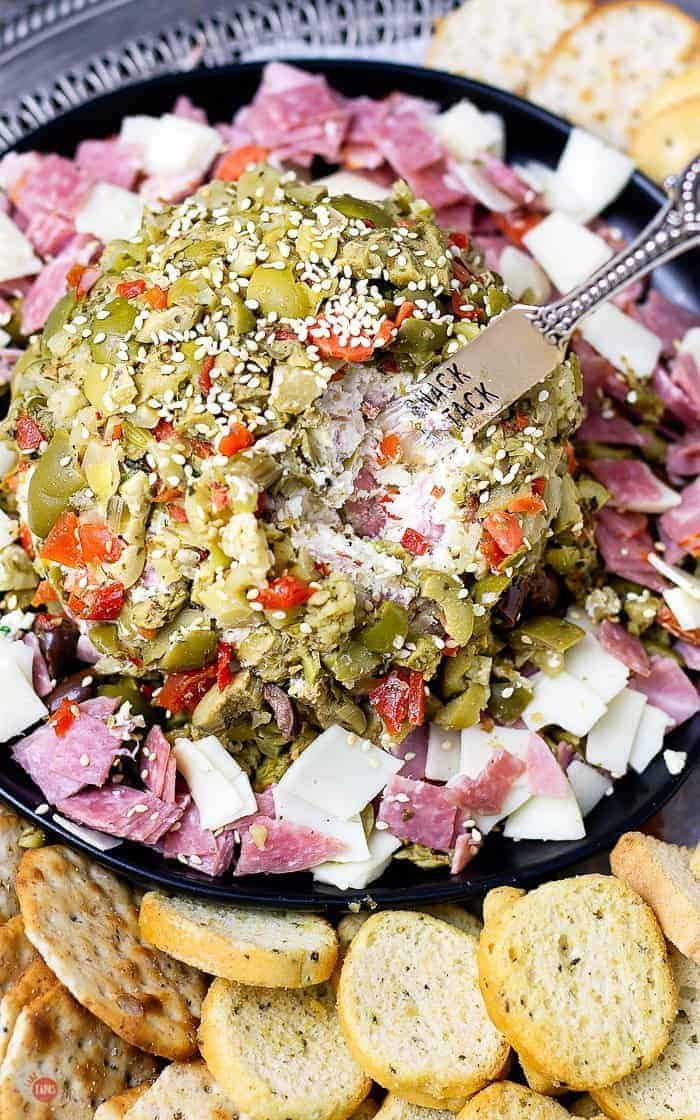 Instead of making a muffuletta sandwich, opt for this delicious muffuletta cheese ball covered in olive salad! #MardiGras #Muffuletta #CheeseBall #PartyFoods
