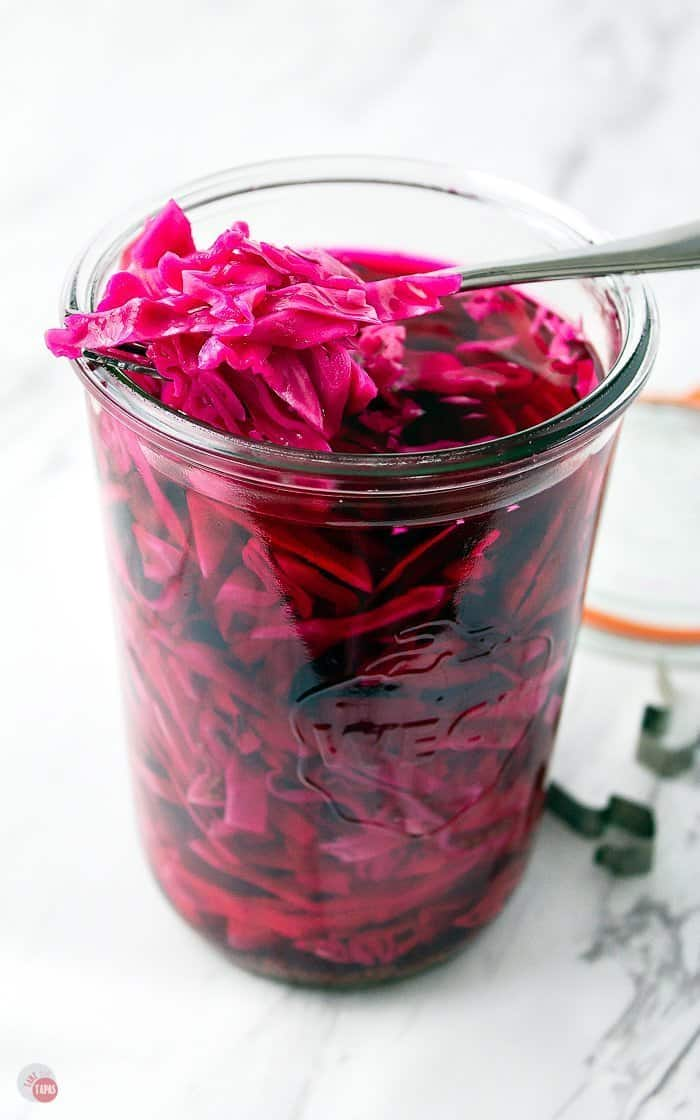 A fork removing pickled red cabbage from a jar