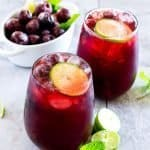 Side angle picture of wine glasses with cherry limeade punch and a bowl of frozen cherries