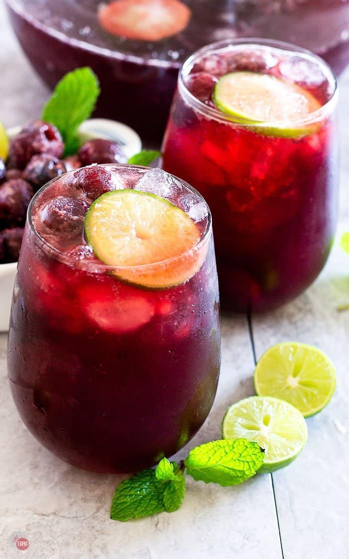 close up of cherry cream soda punch in wine glasses with frozen cherries and lime slices
