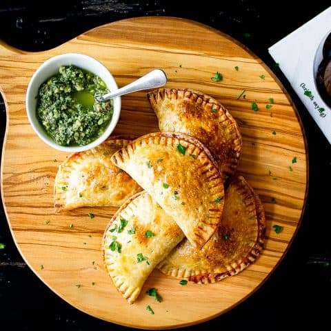 empanadas on a serving board on black table with a drink
