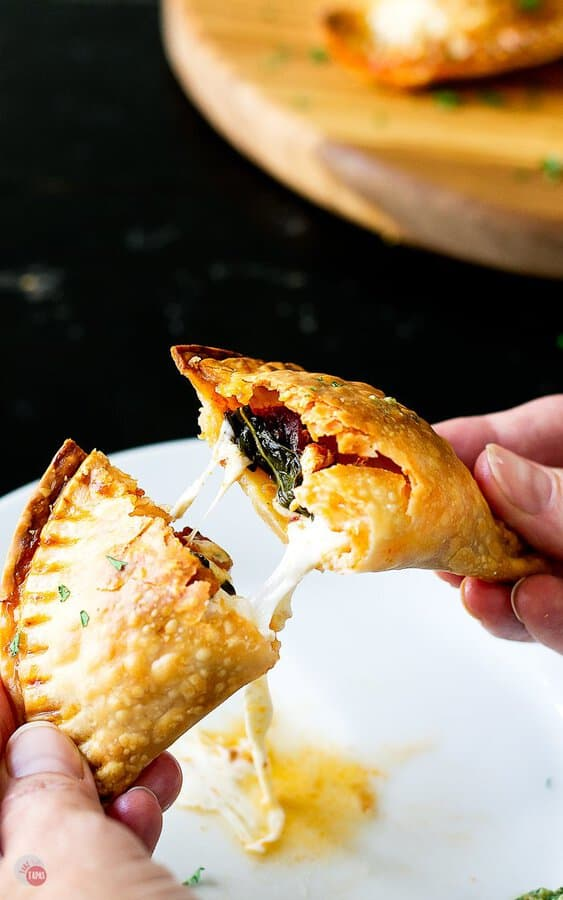 pulling a caprese empanada apart with melty cheese