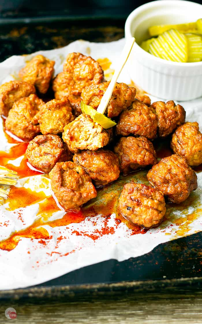 close up of hot chicken meatballs and pickles on toothpicks
