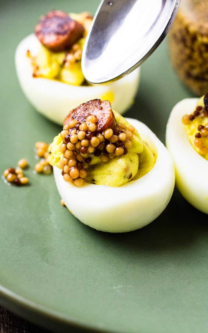 spoon over deviled eggs with mustard seeds