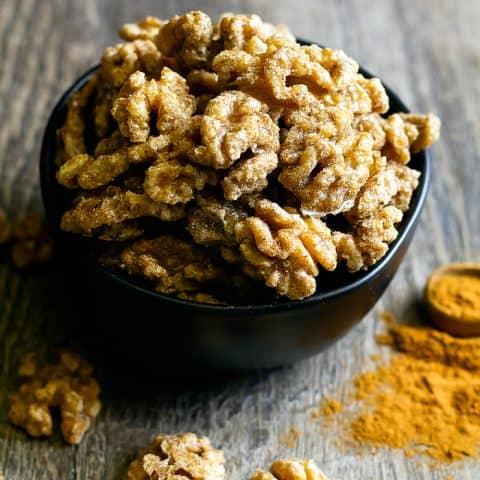 Fall spiced walnuts in a black bowl