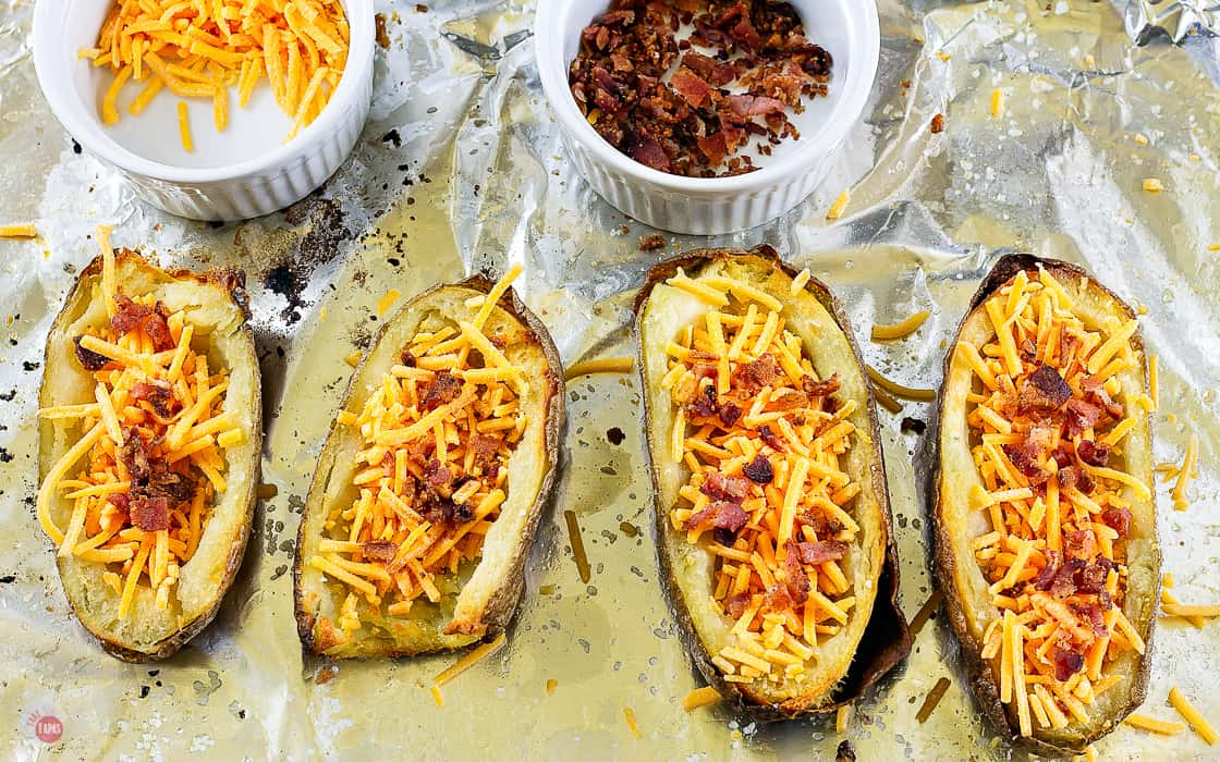 uncooked potato halves with cheese and bacon