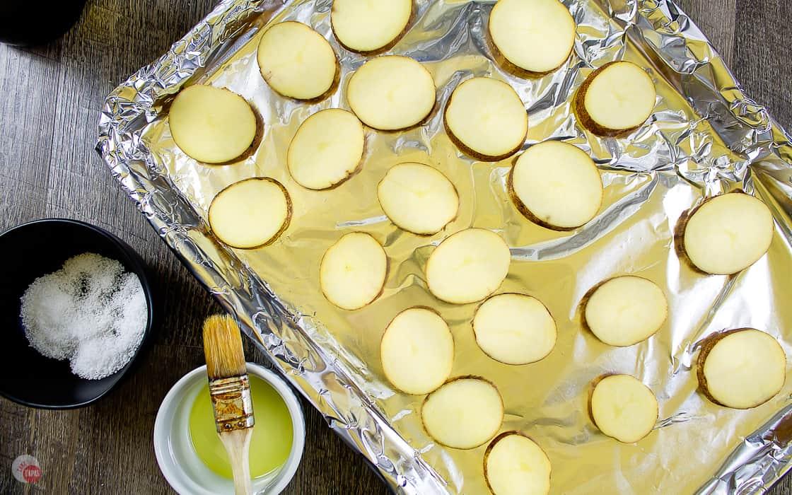 potato slices arranged on a baking sheet