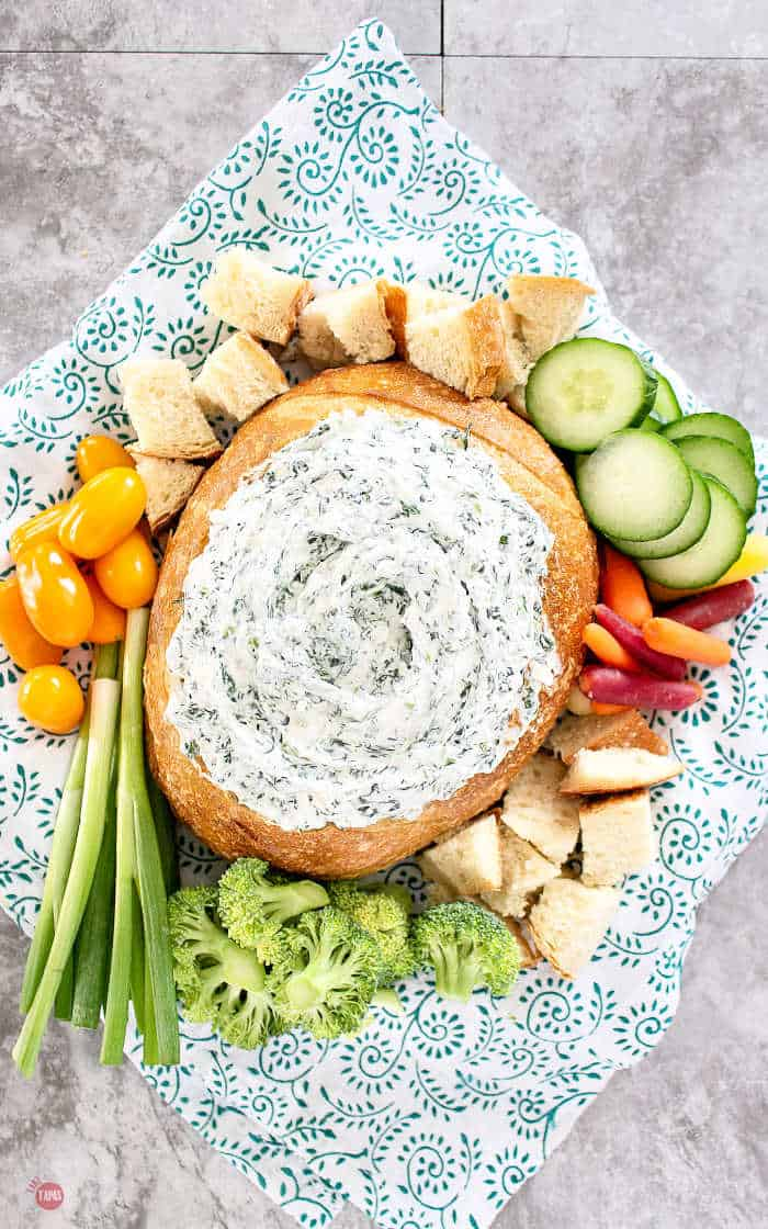 spinach dip in a bread bowl with veggies
