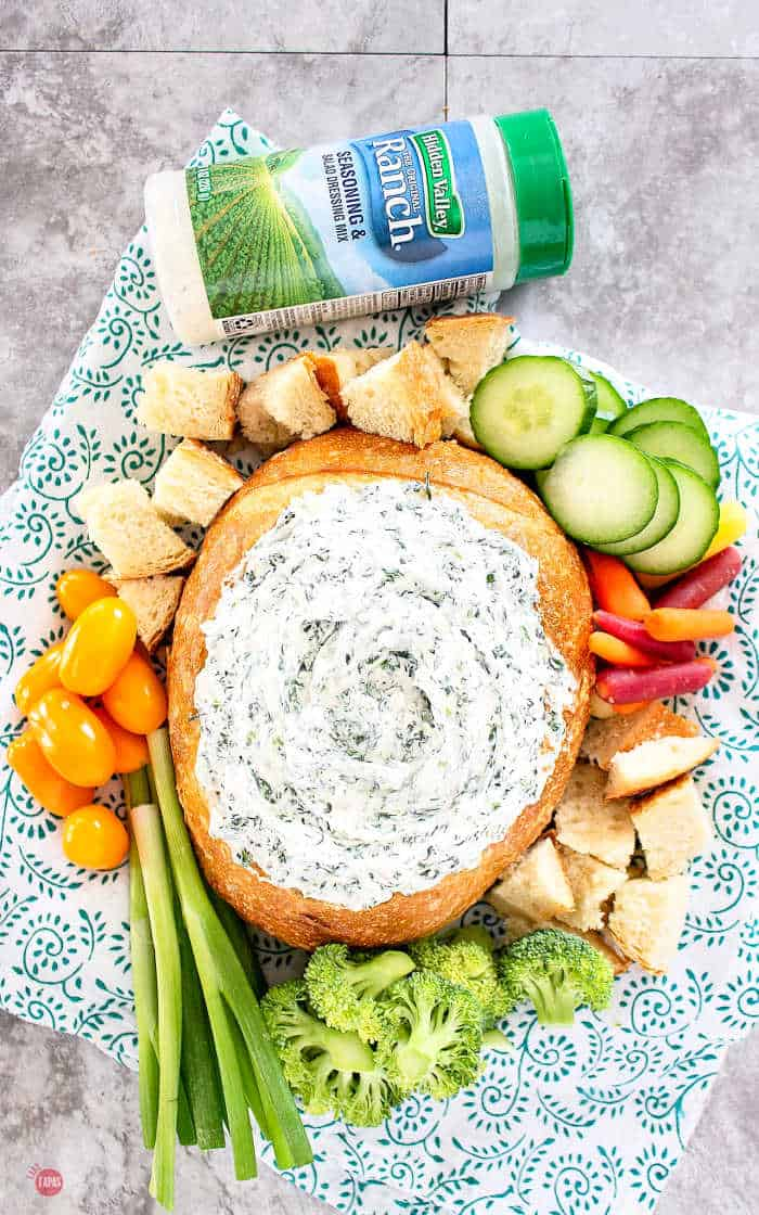 overhead picture of bread bowl with dip and sliced cucumbers