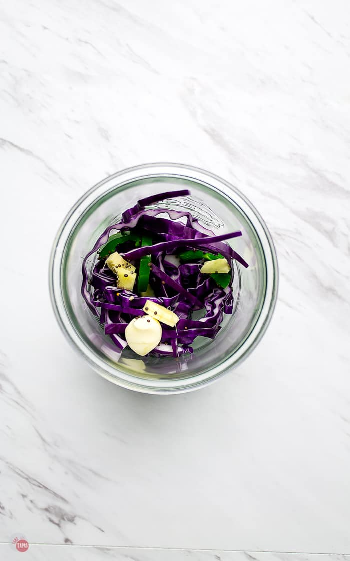 layered cabbage and spices in jar