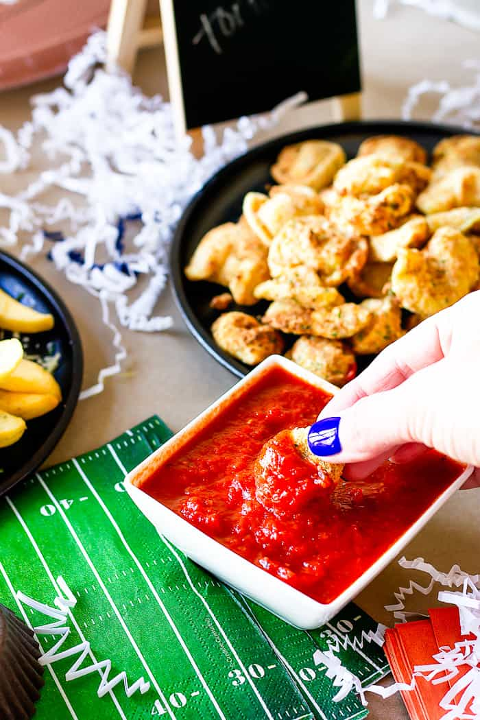 dipping fried tortellini in bowl of tomato sauce