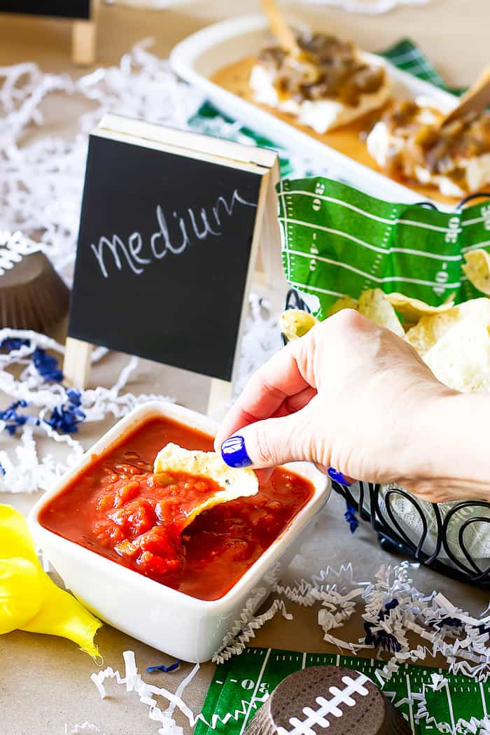 hand dipping a tortilla chip in salsa