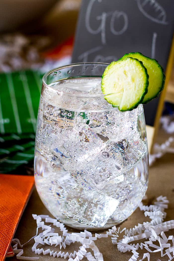 side view of sparkling water cocktail with cucumber garnish