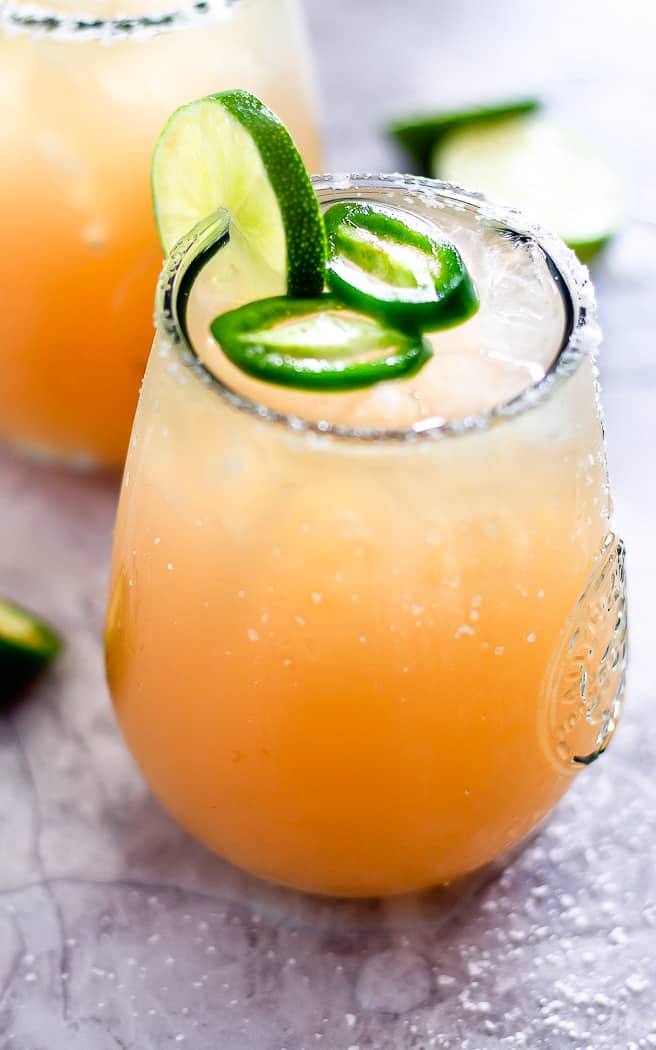 closeup of a paloma drink with jalapeno slices on top and a lime garnish