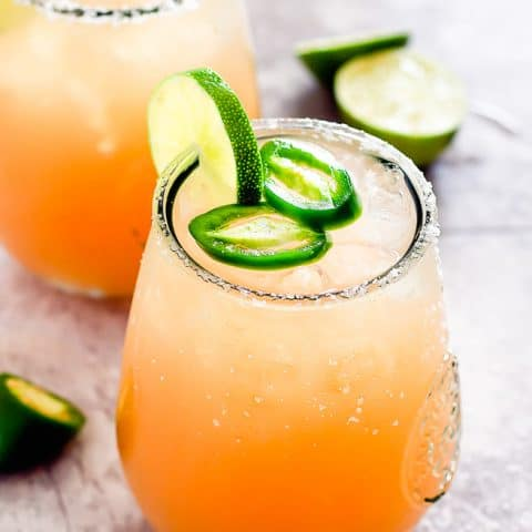 two glasses with cocktail and lime garnish