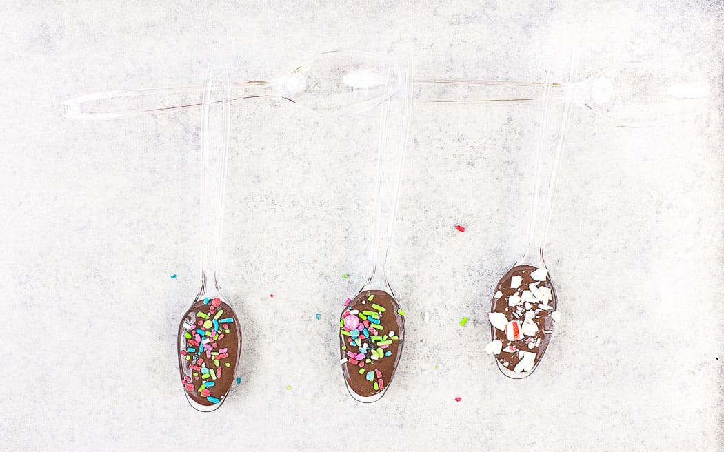 plastic spoons filled with chocolate and sprinkles