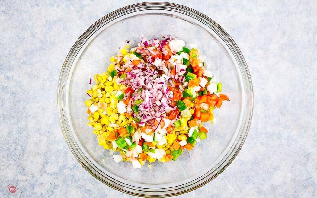 corn in a bowl with pico de gallo and onion