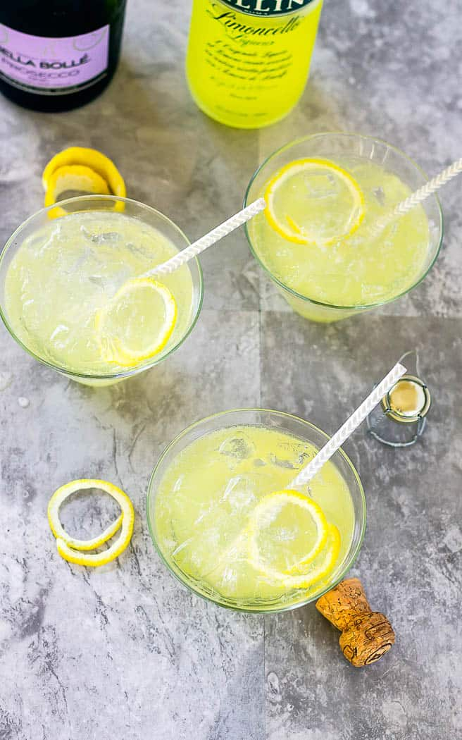 Overhead of 3 LImoncello Ladies with straws in them on a gray surface.