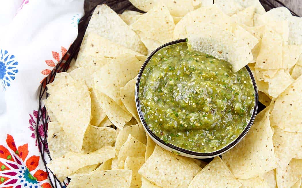 overhead view of green salsa in a bowl surrounded by chips
