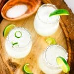 Overhead of three 3-ingredient limeade Margarita's on a wood serving tray