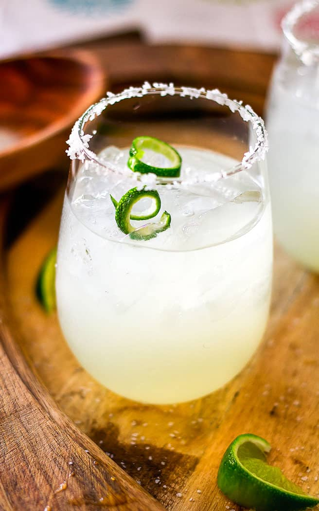 close up of cocktail with lime garnish on wood tray