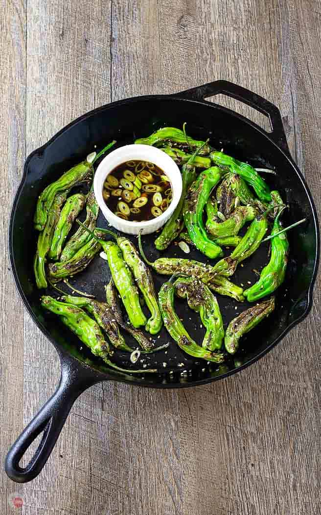 overhead picture of roasted shishito peppers in a cast iron skillet with white bowl of dipping sauce