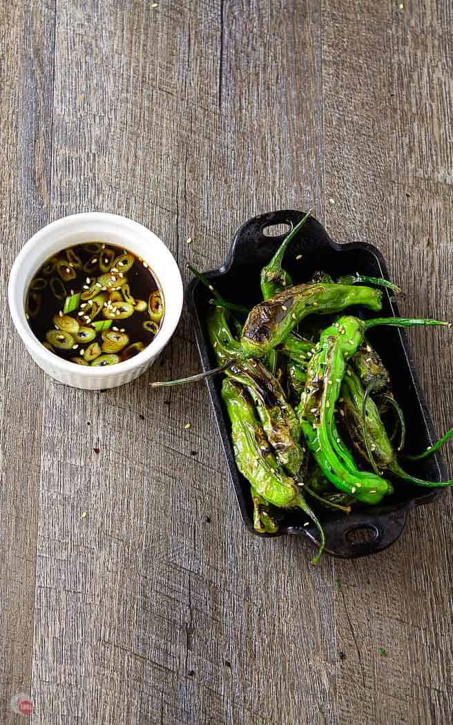 overhead picture of roasted shishito peppers in a cast iron dish with white bowl of dipping sauce