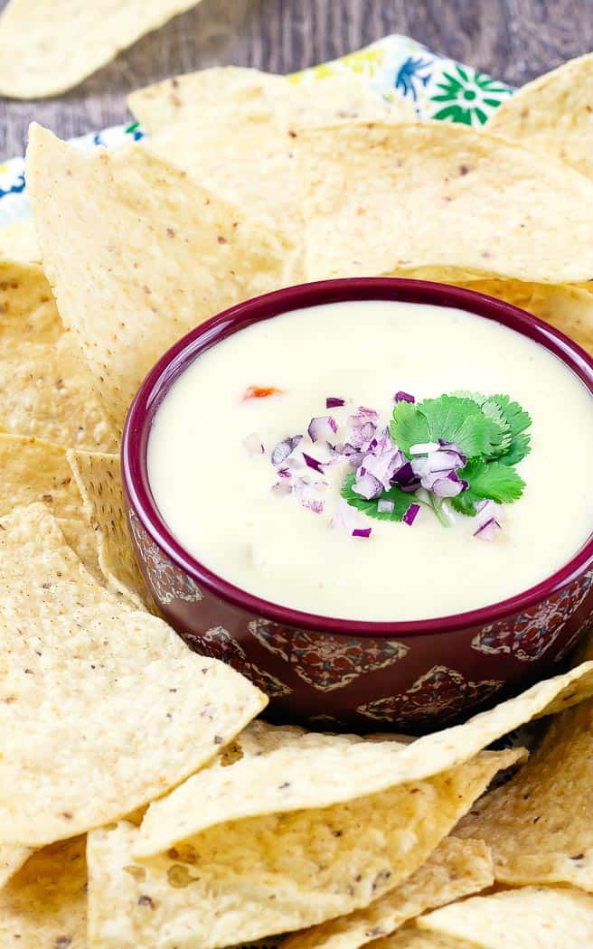 white queso dip in a red bowl topped with onions and cilantro surrounded by chips