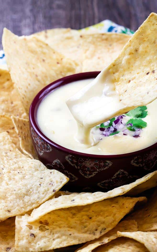 queso dip in a purple bowl surrounded by chips