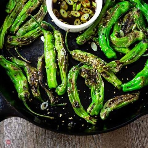 close up of shishito peppers in a casst iron skillet