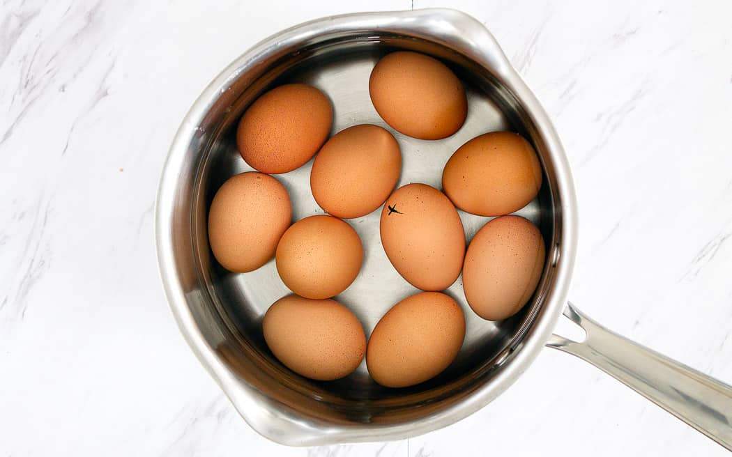 10 brown eggs in a pot with water on a marble surface