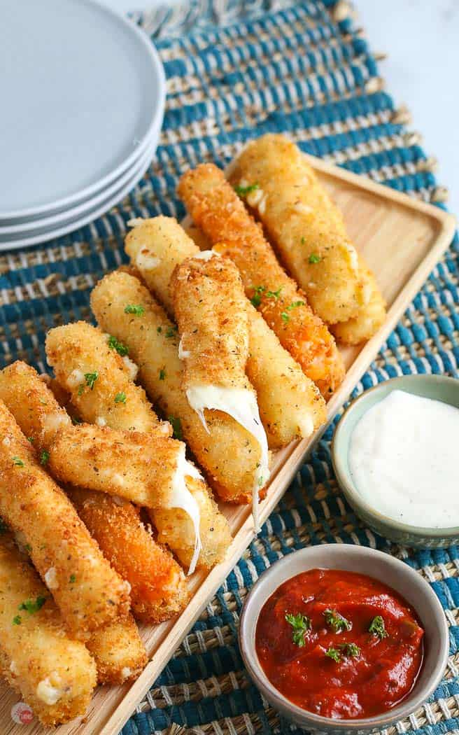 overhead picture of pile of cheese sticks with one broken in half and a small bowl of red sauce and a stack of plates