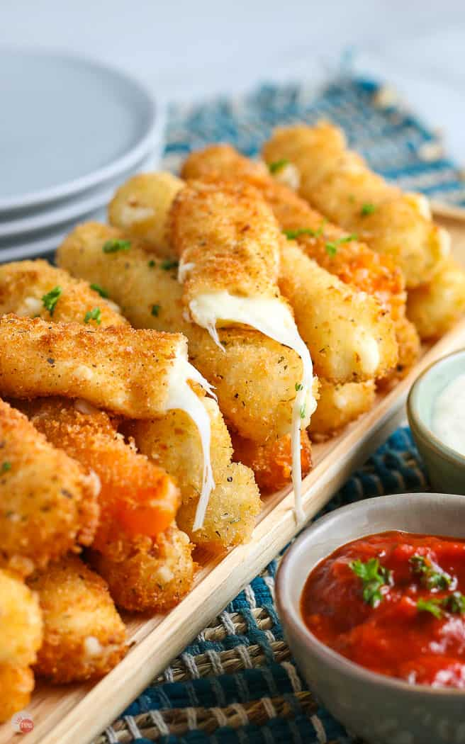 pile of cheese sticks with one broken in half and a small bowl of red sauce