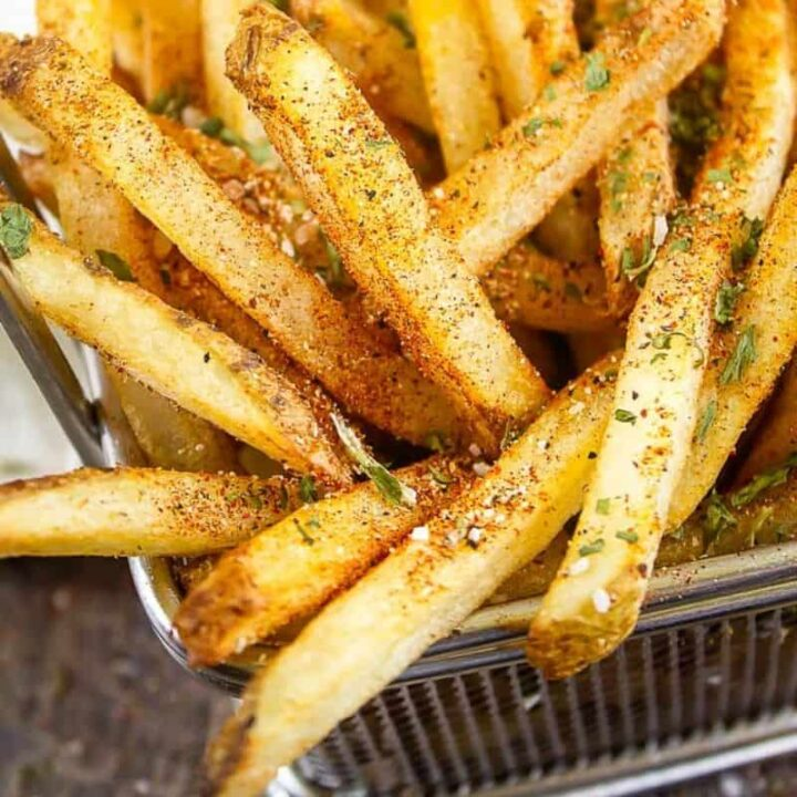 close up of wire basket of french fries with fry seasoning on them